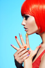 Profile portrait  of a fashion model with  red hairs and multicolor nails.