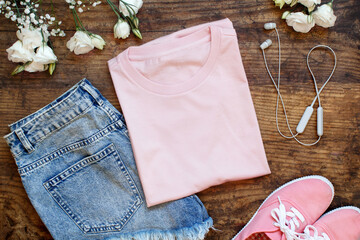 Mockup of a folded t-shirt placed surrounded by trendy aaccessories and flowers