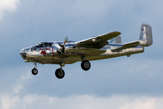 BERLIN - JUN 2, 2016: Red Bull B-25 Mitchell WWII bomber plane about to land during the Berlin Airshow ILA on Berlin-Schoneveld airport