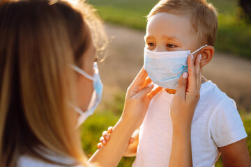 Mother puts on her baby sterile medical mask in the park during pandemic. Covid-2019.