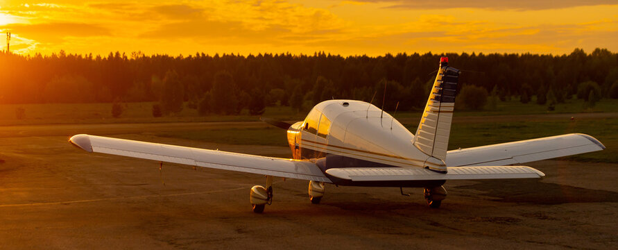 Rear view of a parked small plane on a sunset background. Silhouette of a private airplane landed at dusk.