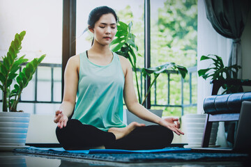 asian woman doing yoga pose at home