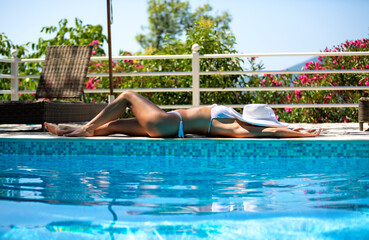 Beautiful woman wearing a white hat is lying by the swimming pool side and sunbathing
