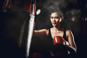 asian woman training with punching bag