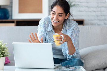 Business woman waving while having an online video call via laptop computer and working remotely...