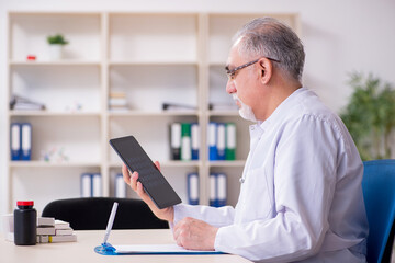 Old male doctor radiologist in telehealth concept