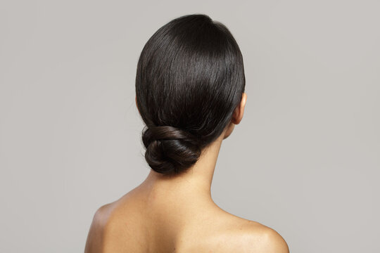 brunette with a smooth bun hairstyle from the back. on gray background
