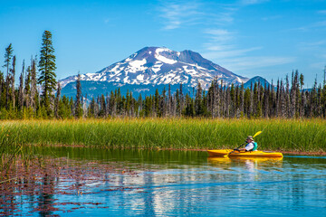 Bend, Oregon;  Hosmer Lake in central oregon, with the south sister reflected in the lake and a man in a kayak paddling by.