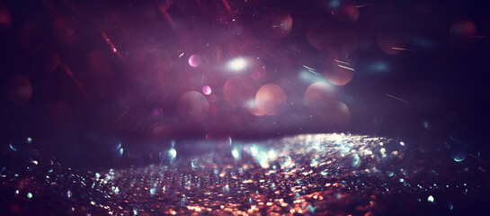 background of abstract glitter lights. gold and purple. de focused