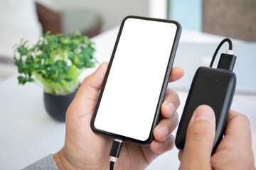 male hands hold phone with isolated screen connected to powerbank