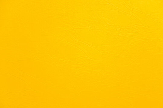 Texture of yellow leather surface, fabric for sewing furniture and other products.