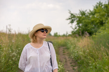 An elderly woman in an elegant straw hat walks along a rural road, enjoying the scenery. The concept of an active lifestyle for older people.