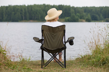 A woman in an elegant straw hat is sitting in a camp chair on the shore of a forest lake, enjoying nature.