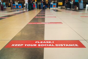 Sticker keep social distance on the floor in the airport check-in lobby, white letters on a red background travel in 2020
