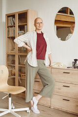 Vertical full length portrait of confident bald woman standing by mirror and looking at camera while posing in minimal home interior, alopecia and cancer awareness