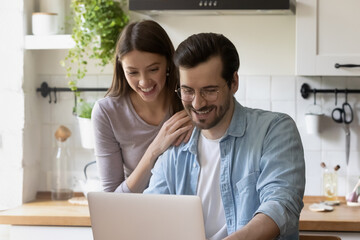 Smiling millennial couple sit at kitchen look at laptop screen shopping on internet together, happy young Caucasian husband and wife browsing surfing web on modern computer, easy technology concept