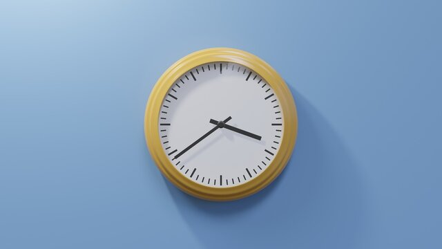 Glossy orange clock on a blue wall at thirty-nine past three. Time is 03:39 or 15:39