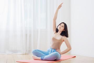 brunette girl doing yoga on  floor at home