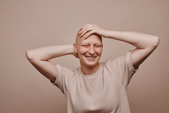 Warm-toned waist up portrait of carefree bald woman touching shaved head and smiling while posing against minimal beige background in studio, alopecia and cancer awareness, copy space