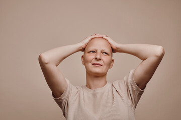 Warm-toned waist up portrait of confident bald woman looking away with hands on head while posing against minimal beige background in studio, alopecia and cancer awareness, copy space