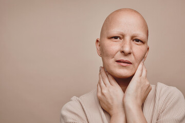 Minimal head and shoulders portrait of bald woman looking at camera while posing against beige background in studio, alopecia and cancer awareness, copy space