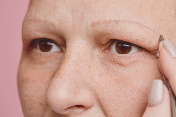 Extreme close up of freckled bald woman drawing eyebrows and doing makeup against pink background in studio, alopecia and cancer awareness, copy space