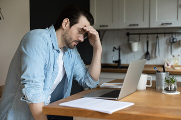 Troubled young Caucasian man sit in kitchen look at laptop screen thinking pondering of problem solution, pensive male freelancer work on computer, make decision studying or analyzing email on gadget
