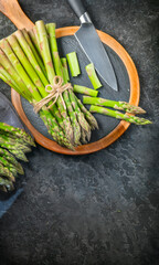 Asparagus. Fresh raw organic green Asparagus sprouts closeup. On black table background. Healthy vegetarian food. Raw vegetables, market. Healthy eating concept, diet, dieting. Top view, flat lay
