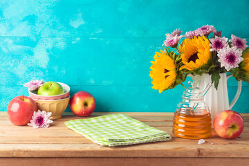 Jewish holiday Rosh Hashana background with honey jar, apples and sunflowers on wooden table. Kitchen counter with tablecloth and copy space for product display