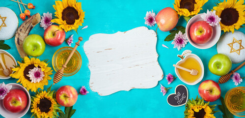 Jewish holiday Rosh Hashana background with honey, apple and sunflowers on blue wooden table. Top view from above