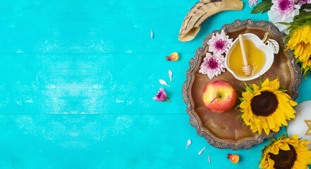 Jewish holiday Rosh Hashana background with honey, apples and sunflowers on blue wooden table. Top view from above