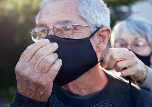 Active senior couple on outdoor walk wearing face masks