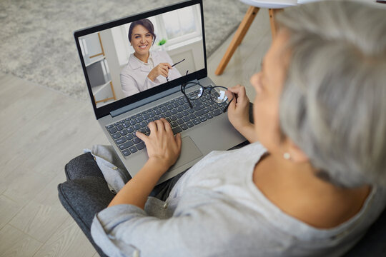 Doctor online. Above view of senior patient talking to doctor online from home. Mature woman consulting with GP on laptop