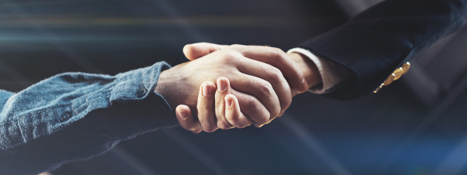 Business people shaking hands in office after successful deal and partnership. Wide screen, panoramic
