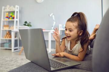 Little girl talking to family, friend or school teacher online from home. Lovely kid using laptop...