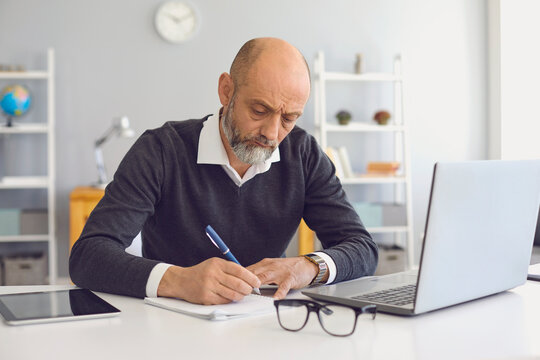 Working and studying from home. Thoughtful mature man taking notes during online business meeting or webinar