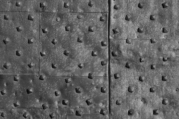 Very old rusty iron door with studs as background (Black and White)