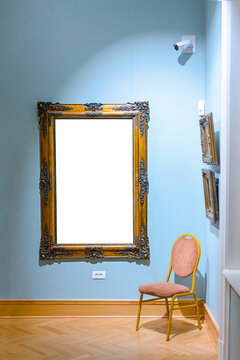 Big old luxury antique black and golden frame in a galery with a chair in the corner