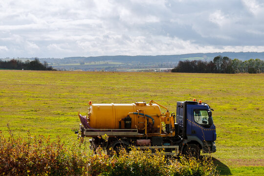 Septic truck on field with grass. Sewage Tank truck. Sewer pumping machine.