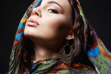 portrait of beautiful young woman in color veil and jewelry