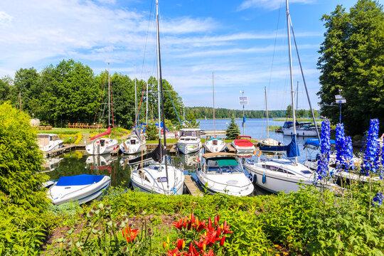 Sailboats mooring in small marina Janus full of colorful flowers near Ruciane Nida town, Mazury Lake District, Poland