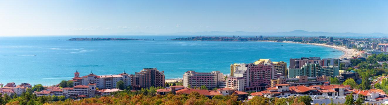 panorama of the sunny beach bay. popular destination of bulgaria. famous resort town nessebar on an island. mountain ridge in the far distance. velvet season
