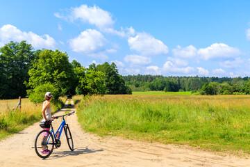 Young woman cycling on bike on forest road near Mikolajki town, Masurian Lakes, Poland
