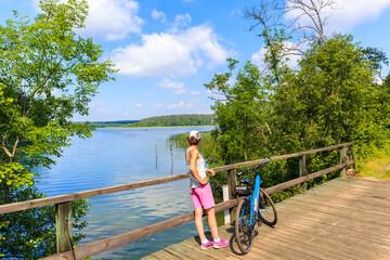 Young woman standing with bike on bridge and looking and Mokre lake near Krutyn village, Masurian Lakes, Poland