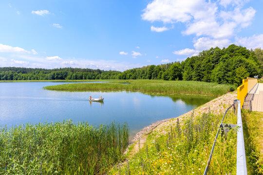 MOKRE LAKE, POLAND - JUN28, 2020: Couple of people sailing with small fishing boat on Krutynia river to Mokre lake, Masurian Lakes, Poland.