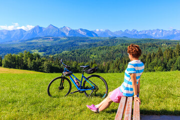 Young female biker sitting on bench on meadow and looking at panorama of Tatra Mountains on beautiful summer sunny day at Lapszanka Pass, Poland