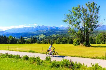 Young female biker cycling along Tatra Mountains on beautiful summer sunny day at Lapszanka Pass, Poland