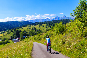 Young female biker cycling from Lapszanka Pass to Osturnia village in Tatra Mountains on beautiful summer sunny day, Slovakia