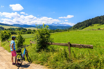 Young female biker looking at Tatra Mountains on beautiful summer sunny day near Kacwin village on Poland Slovakia border