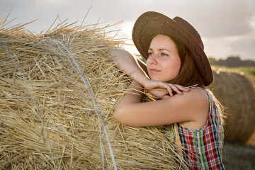 Fototapete - Young girl in a cowboy hat on hay bale. Girl farmer in denim shorts and plaid shirt, in a wheat field in sunset. Happy Woman cowgirl on a farm. Freedom lifestyle.